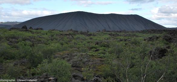 Les pentes régulières du cône de scories Hverfjall, vu depuis le champ de lave aux rochers noirs torturés bordant à l'Est le lac Mývatn (Islande)
