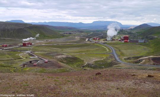 Forages, conduites forcées, tours de refroidissement et bâtiments rouges vifs de la centrale géothermique du Krafla (Islande), prise depuis les pentes Sud du volcan
