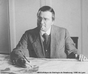 Émile Argand (1879-1940) devant une carte de l'Asie