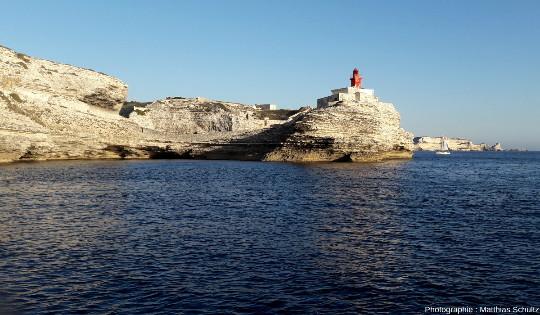 Vue depuis la mer, en direction du Sud-Est, du phare de la Madonetta, qui signale l'entrée très protégée et presque insoupçonnable du port de Bonifacio où rentre un voilier