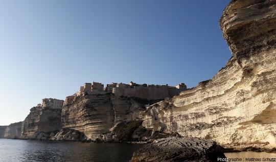 Vue sur Bonifacio depuis la mer au Sud-Est, montrant un important surplomb des falaises, y compris sous la vieille ville, et des chaos de blocs éboulés