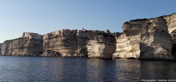 """Vue depuis la mer en direction du Nord-Ouest sur le «grain de sable», la vieille ville de Bonifacio, les falaises en surplomb, et les blocs écroulées """"en masse"""" à droite de l'image"""