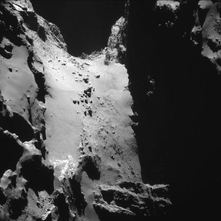 Vue (sous un autre angle que dans l'image précédente) de plusieurs entonnoirs d'effondrement (à gauche) situé au-dessus du cou de la comète 67P/CG