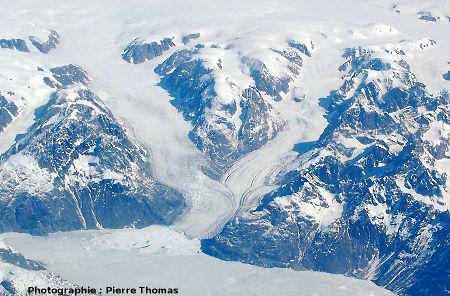 Confluence, fluage et écoulement ductile de glaciers se jetant dans un fjord encore gelé de la côte orientale du Groenland.