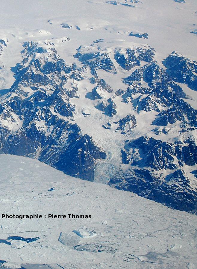 Un autre glacier se jette dans la mer (encore prise par les glaces) par l'intermédiaire d'une zone de séracs, côte orientale du Groenland