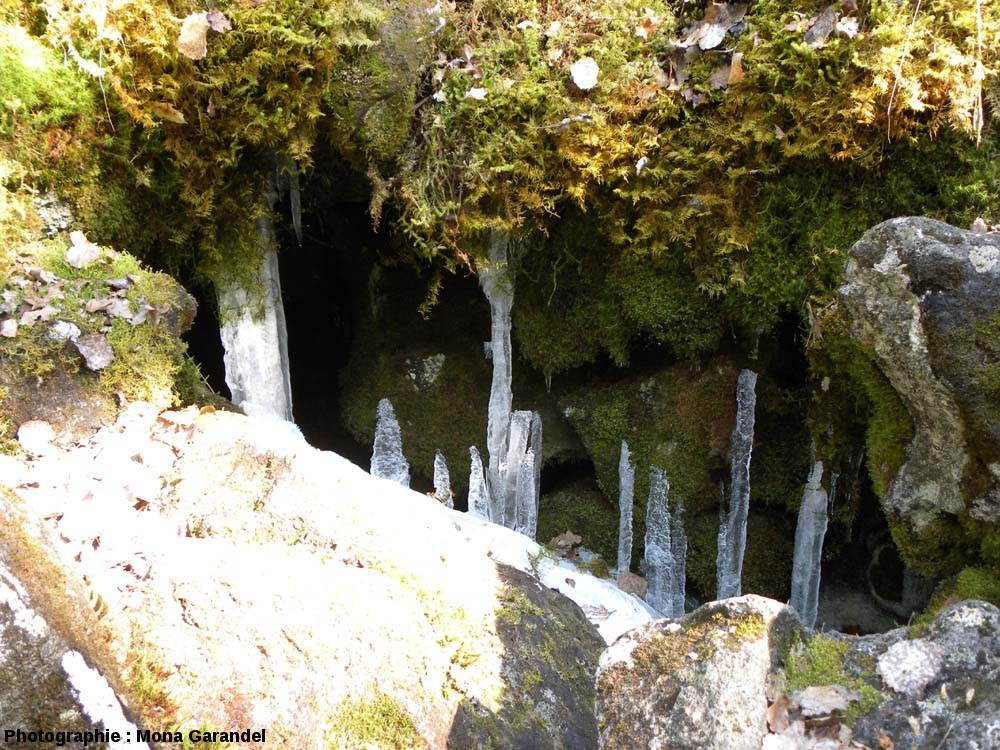 Stalactites et stalagmites de glace dans des cavités au fond d'un «trou à glace» de la cheire du Puy de Côme