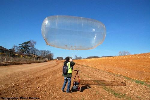 Stéphane Nys (Air Tech Photo) installant un appareil photo sous le ballon qu'il s'apprête à lancer