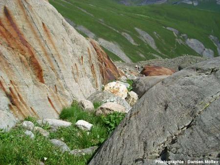 Trainées d'oxydes ferriques colorant une paroi de roche affectée par des stries glaciaires, secteur du lac des Quirlies, Massif des Grandes Rousses (Isère).