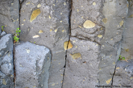 Nodule de péridotite fracturé par une limite de prisme dans le sous-bassement d'une maison située au centre de Burzet sur le bord de la Bourges, Ardèche
