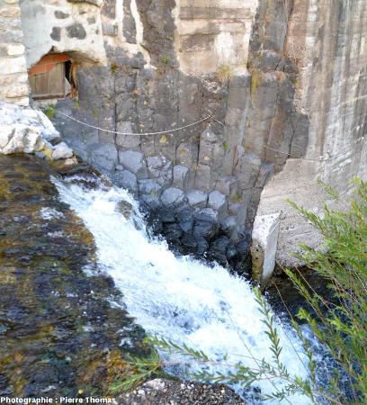Colonnades de basalte montrant un nodule de péridotite fracturé par une limite de prisme dans le sous-bassement d'une maison située au centre de Burzet sur le bord de la Bourges, Ardèche