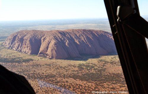 Vue d'hélicoptère rapprochée montrant les faces Nord-Est (au soleil) et Nord-Ouest (à l'ombre) d'Uluru