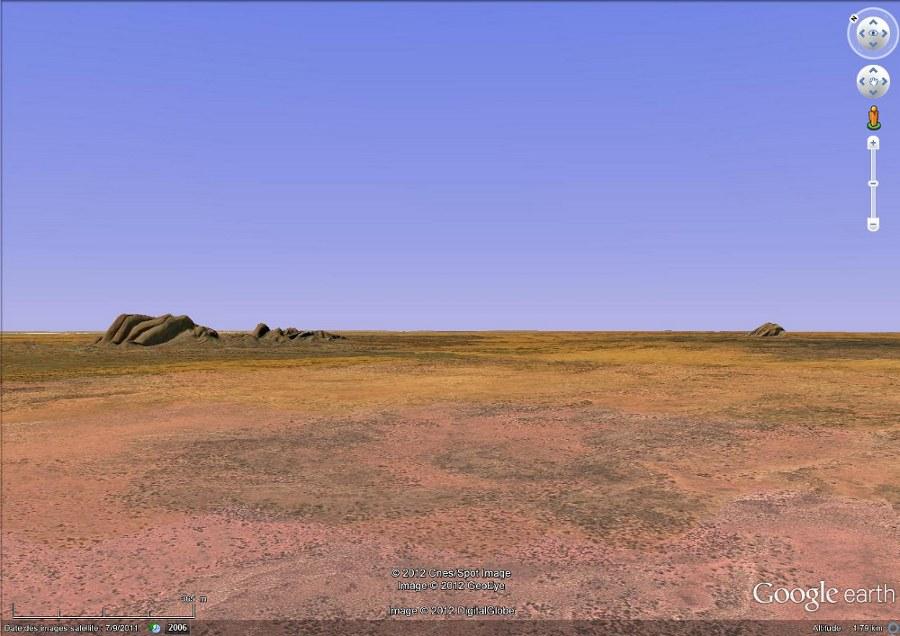 Vue rasante montrant les Taka Tjuta, à gauche, et Uluru, au fond à droite, distant de 30km