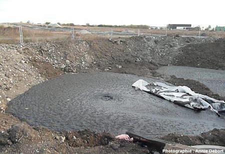Le petit bassin provisoire bien rempli de pétrole et débordant un peu plus dans l'agrandissement creusé sur la droite