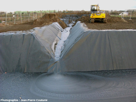 """Un mois après le début de l'éruption, un bassin définitif """"bâché et imperméabilisé"""" a été construit, relié au bassin provisoire par un chenal d'amenée, lui aussi bâché"""