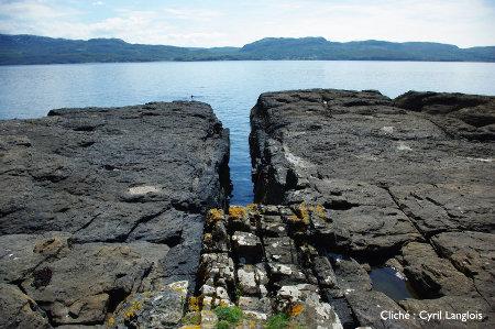 Tranchée creusée par l'érosion dans un dyke de basalte inséré dans des pélites noires, île de Skye, Écosse