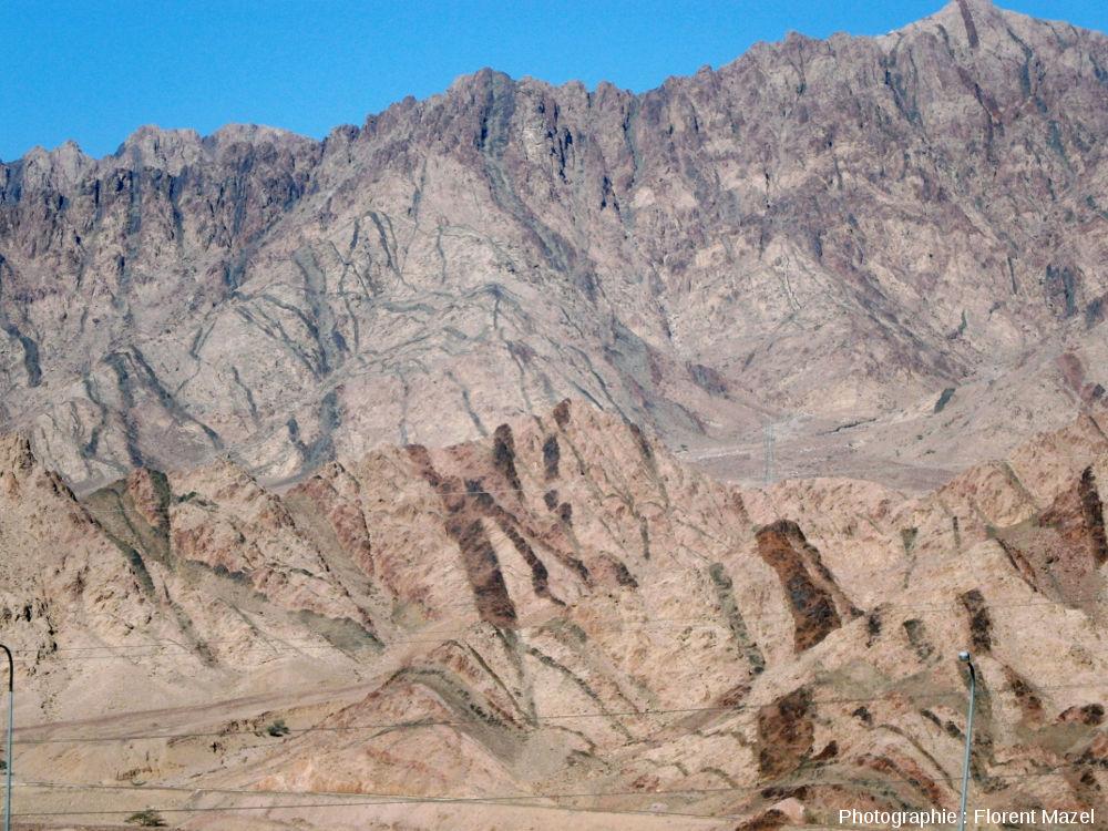 Réseaux de dykes noirâtres et rougeâtres en bordure de route, à une dizaine de kilomètres à l'Est d'Aqaba (Jordanie)