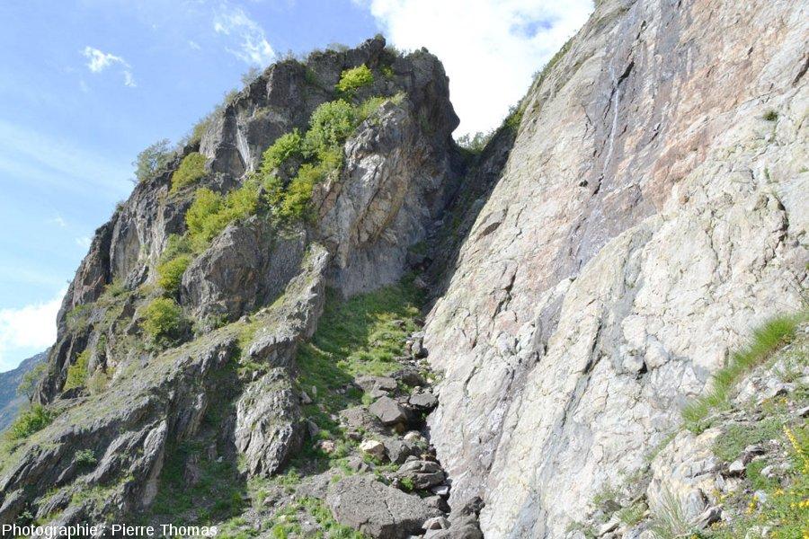 Gros bloc pluri-décamétrique fait de roches résistantes (basalte, dolomie, calcaire) anciennes, bloc emballé dans les calcaires marneux du Lias supérieur