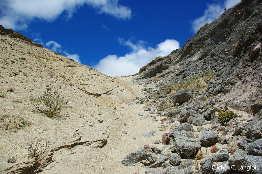 Contact entre des cendres (blanches, à gauche) et un dôme de laves andésitico-dacitiques sous-jacent (gris-bleues, à droite), près de la crête du Quilotoa