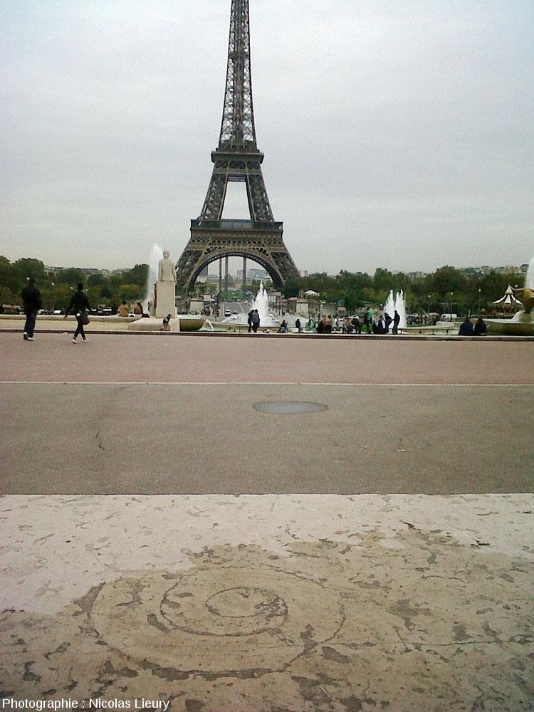 Ammonite de belle taille dans une dalle calcaire de l'esplanade du Trocadéro sur fond de Tour Eiffel, Paris
