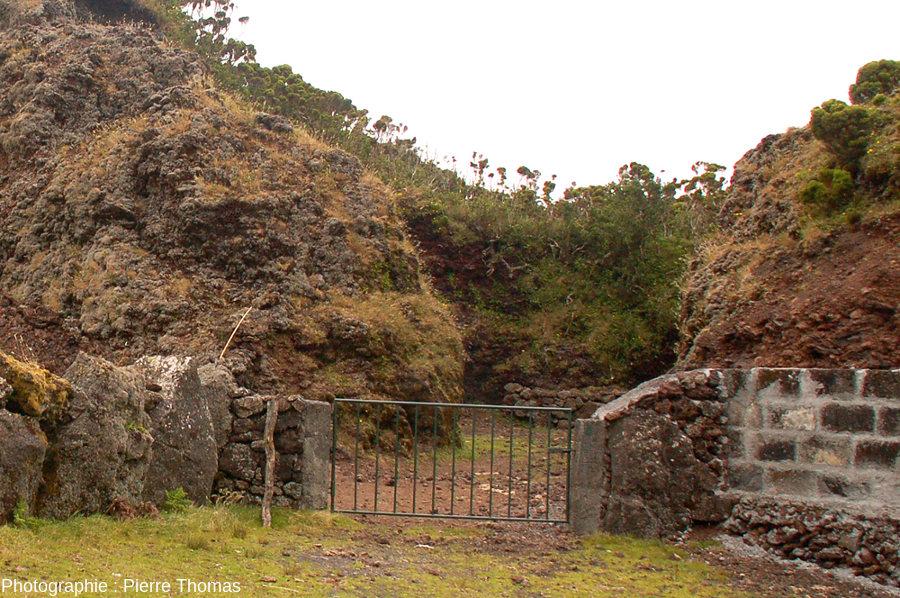 Vue rapprochée de l'égueulement du cratère permettant de voir (1) les aménagements internes et externes réalisés par les éleveurs et (2) la raideur des flancs internes du cratère