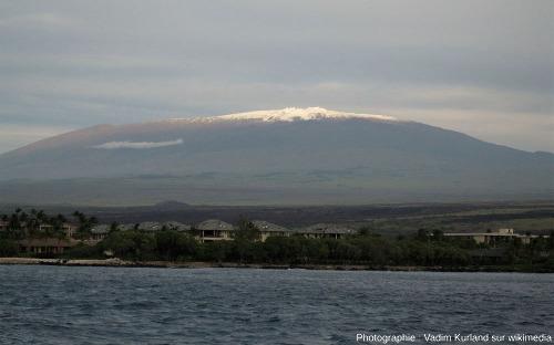 Le sommet enneigé du Mauna Kea vu depuis la côte au climat tropical
