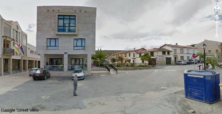 """Le musée d'Igea (à gauche, là où il y a les drapeaux) sur la place d'Igea, place """"surveillée"""" par un dinosaure (à droite)"""