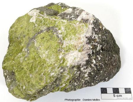 Fragments de coussin basaltique montrant de gros ferro-magnésiens noirs automorphes (pyroxènes?), des vacuoles remplies de calcite et des fractures remplies de calcite (blanche) et d'épidote (verte)