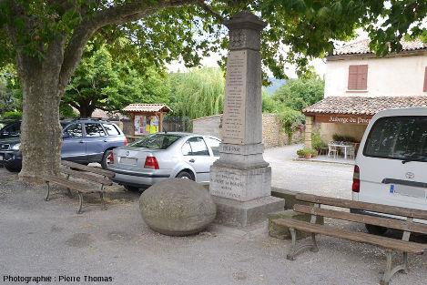 Une boule de grès albien déposée sur la place centrale du village de Saint-André-de Rosans, au pied du monument aux morts