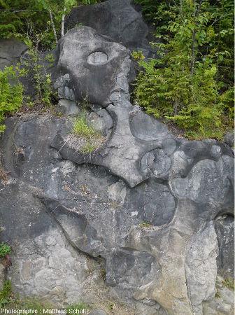 Falaise verticale percées de cylindres horizontaux, les paléomarmites de géant de Pointe-au-Pic, Québec