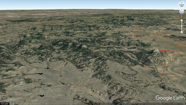 Vue aérienne du complexe volcanique (ou crypto-volcanique) de la Tour du Diable, Devils Tower (à droite, flèche rouge), et des Missouri Buttes (au centre et à gauche)