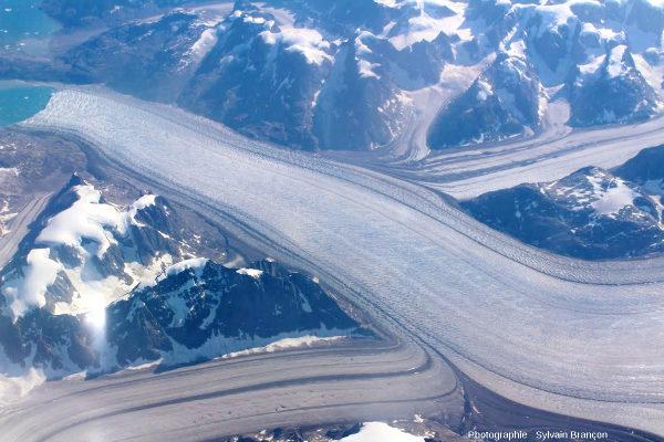 Confluences entre un glacier principal venant de droite et recevant un glacier secondaire sur sa rive gauche, et deux autres glaciers secondaires sur sa rive droite, côte Est du Groenland (vers 63° lat. N)