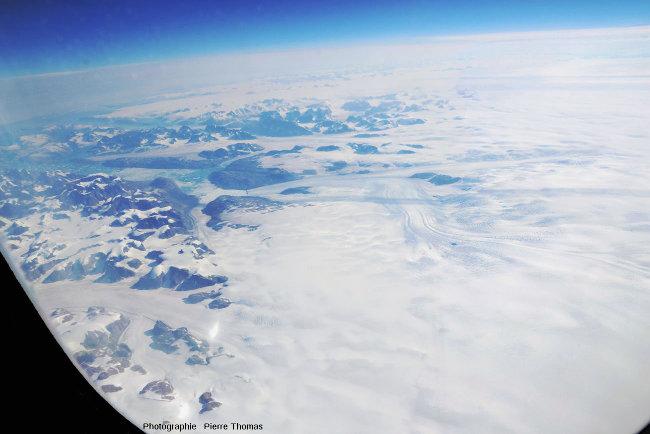 Vue sur la calotte glaciaire du Groenland qui occupe la moitié droite de l'image, et sur des glaciers qui s'en échappe