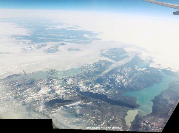 De gauche à droite, l'extrémité Ouest de la calotte groenlandaise, une bande de terre et de lacs dans lesquels se jettent des glaciers, et un couvert nuageux masquant la côte et la mer du Labrador