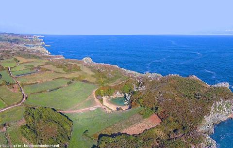 Vue aérienne globale du plateau calcaire au Sud de Naves (Asturies), de sa falaise bordière et de la doline de Gulpiyuri à marée montante