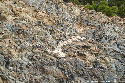 Grosse poche de gabbro (roche claire) entourée de dunite (roche noire) au sein d'une harzburgite (roche orangée et grisâtre), dunite et harzburgite étant relativement serpentinisées, Troodos, Chypre