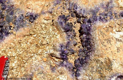 Zoom sur le centre de la photo précédente où l'on voit que la cristallisation d'améthyste n'a pas complètement rempli la fracture en laissant une cavité tapissée des pointes pyramidales de quartz violet: une géode, également appelée druse