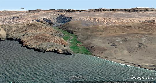 """Vue aérienne """"proche"""" de la vallée du rio Ocoña, fleuve venant de la Haute Cordillère des Andes (dont on devine quelques sommets enneigés) et traversant le désert côtier"""