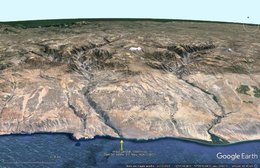 Vue aérienne lointaine de la vallée du rio Ocoña, fleuve venant de la Haute Cordillère des Andes (dont on devine quelques sommets enneigés) et traversant le désert côtier