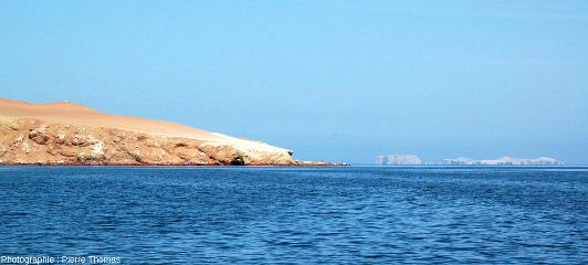 Les iles Ballestas (au fond à droite) à 10km de la côte du Pérou (à gauche), où l'on voit aussi des dépôts blancs de guano