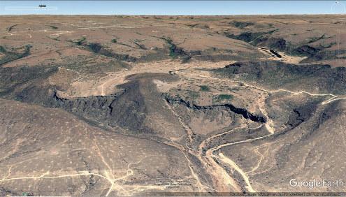 Vue aérienne de la plaine alluvio-travertineuse du Wadi Darbat (Oman) derrière son barrage de travertin