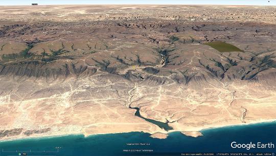 Vue aérienne plus lointaine de la vallée du Wadi Darbat (Oman) au centre de l'image, juste au Nord de la faille normale bordant la plaine côtière