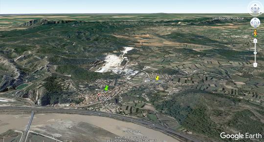 Vue aérienne de la ville d'Orgon et des carrières d'Omya (tâche blanche) au pied du massif des Alpilles
