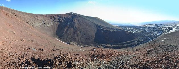 Mosaïque de photos couvrant 180° montrant le cratère égueulé d'un cône de scorie et la coulée de basalte qui en sort, province volcanique du Payun Matru, Argentine