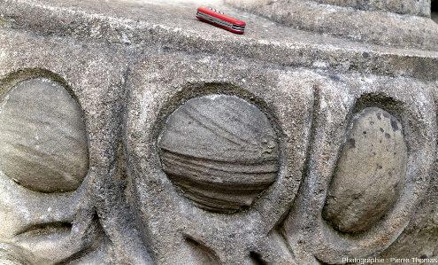 Balustrade en béton englobant une boule de grès dans laquelle on voit très bien des stratifications entrecroisées, Palais idéal du facteur Cheval
