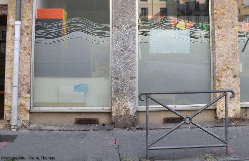 Devanture d'un magasin (fermé pendant le confinement) dont les piliers sont en calcaire à gryphées