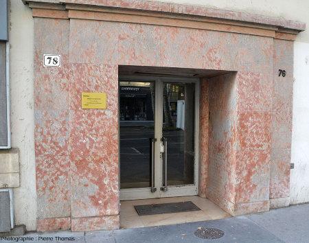 Entrée d'immeuble à encadrement de dalles de calcaire rose riche en cavités pleines de calcite (cavité appelée stromatactis, dont l'origine est discutée)