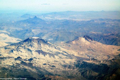 Les volcans Descabezado Grande (à gauche, 3953m), et Cerro Azul (à droite, 3788m) photographiés par le hublot d'un avion d'une ligne aérienne intérieure chilienne