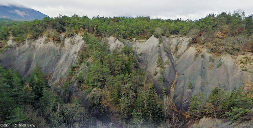 Vue Google Street view du contact stratigraphique entre terrains lacustro-glaciaires du Würm (gris-beige clair) reposant sur les marnes noires du Bathonien