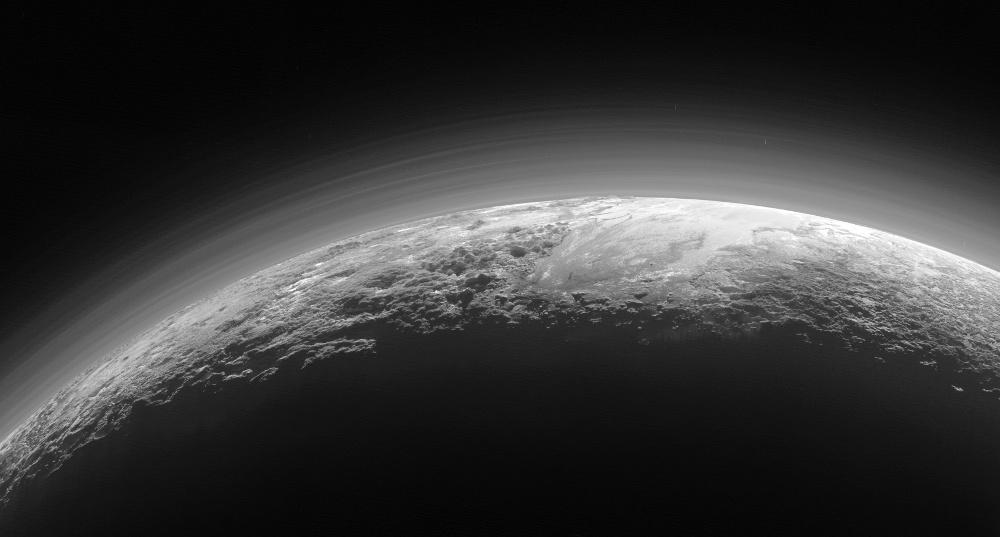 Fin croissant de Pluton surmonté d'une atmosphère que l'éclairage révèle très zonée, avec une douzaine de niveaux de brume superposés