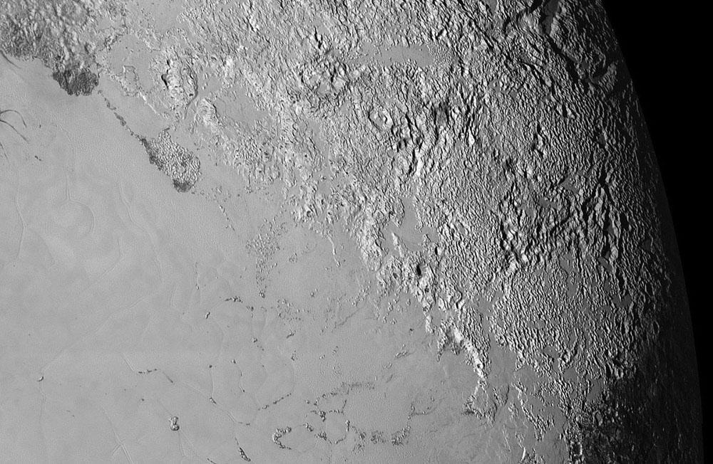 """Partie Est du """"cœur"""" de Pluton, nommé Tombaugh Regio (en haut à droite), à l'Est de Sputnik Planum (en bas à gauche)"""